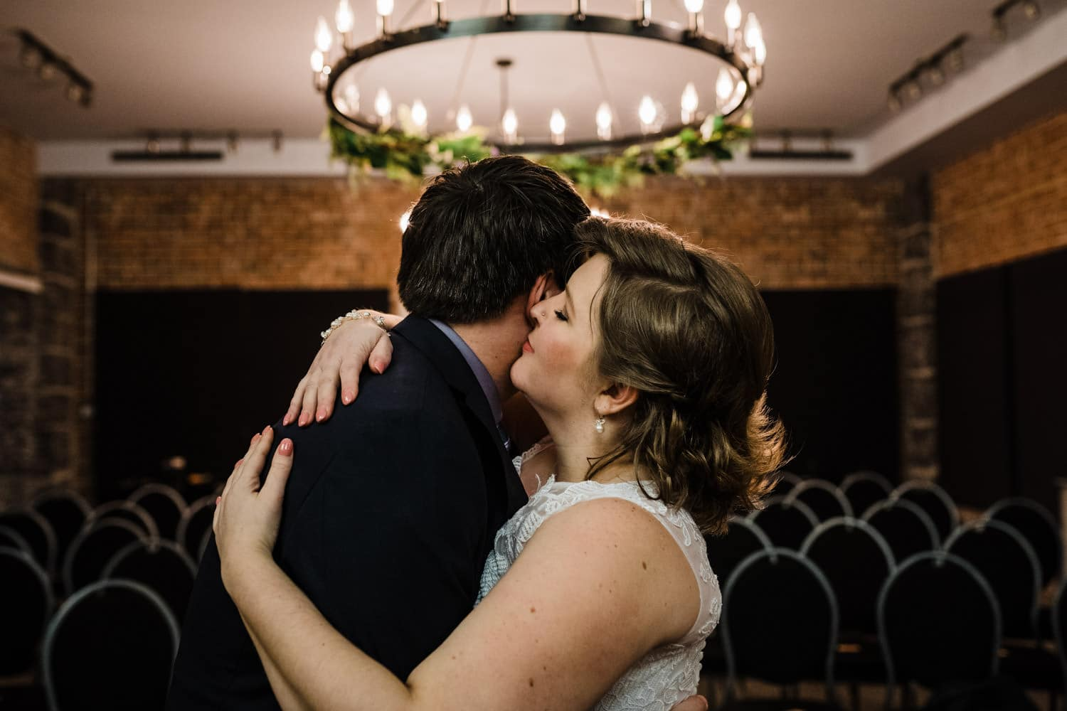 bride and groom hug under a chandelier at intimate winter wedding