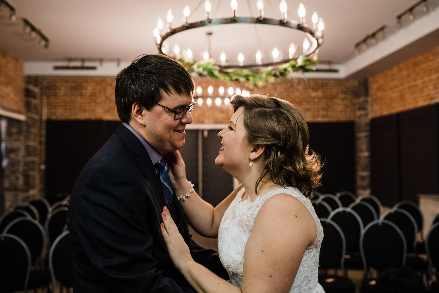 bride and groom laugh together in small chapel