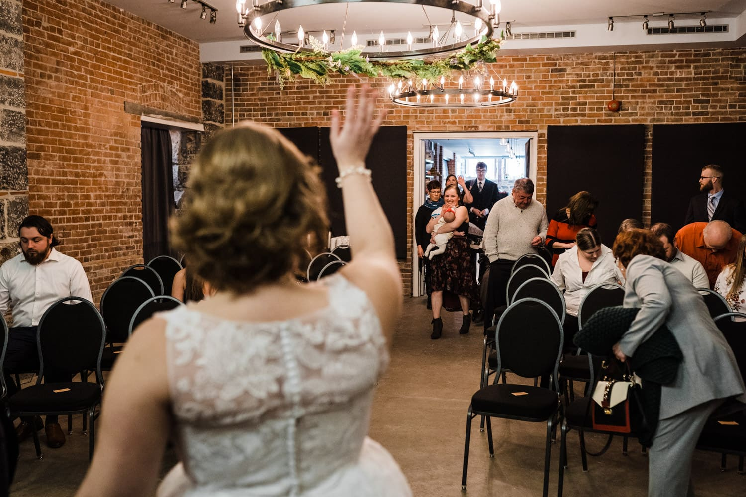 bride waves at her guests as they enter chapel