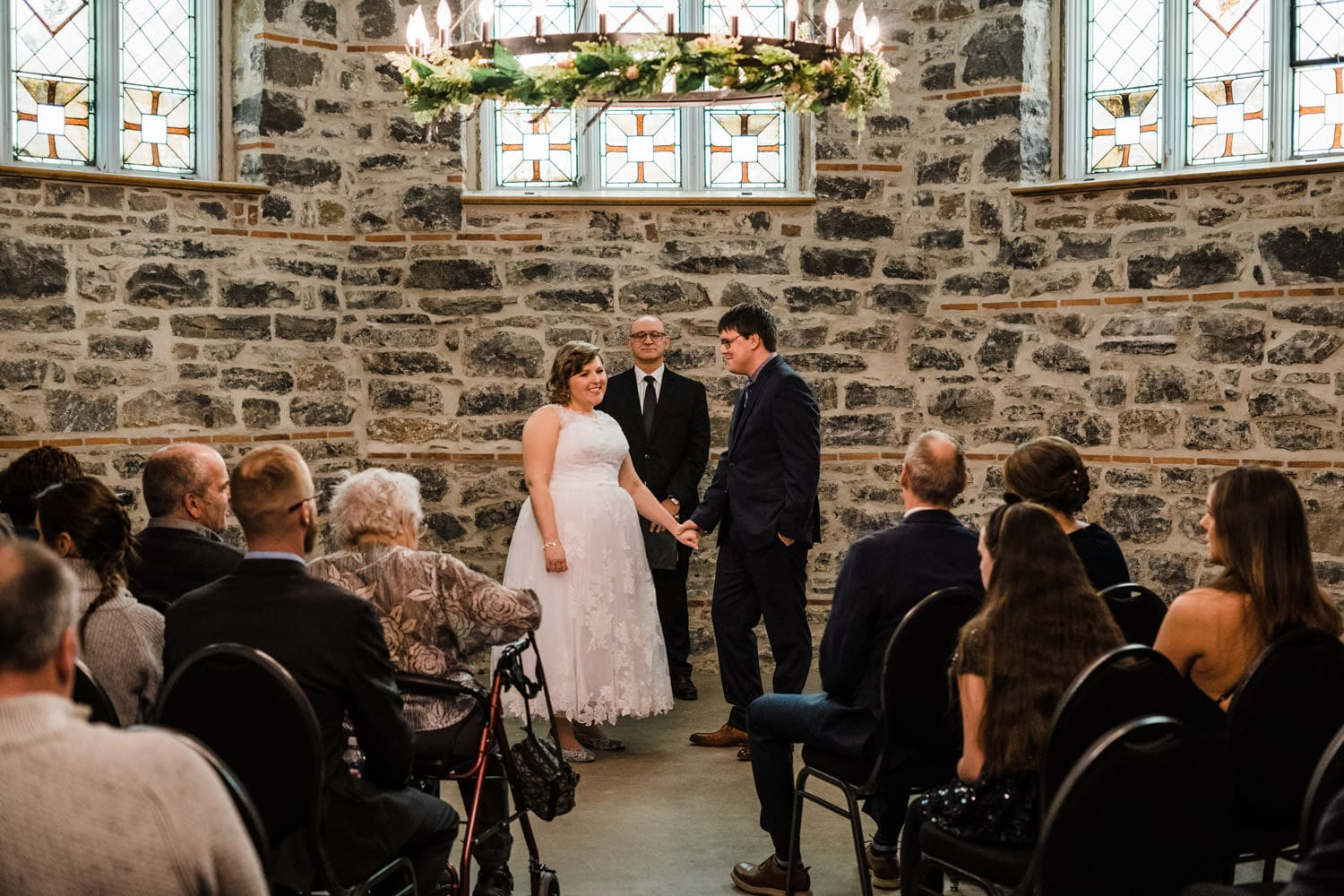 bride and groom look out at their guests in small chapel