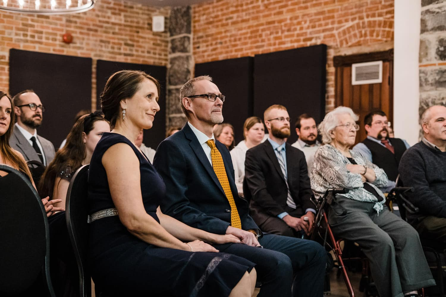 groom's parents look on during intimate winter wedding ceremony