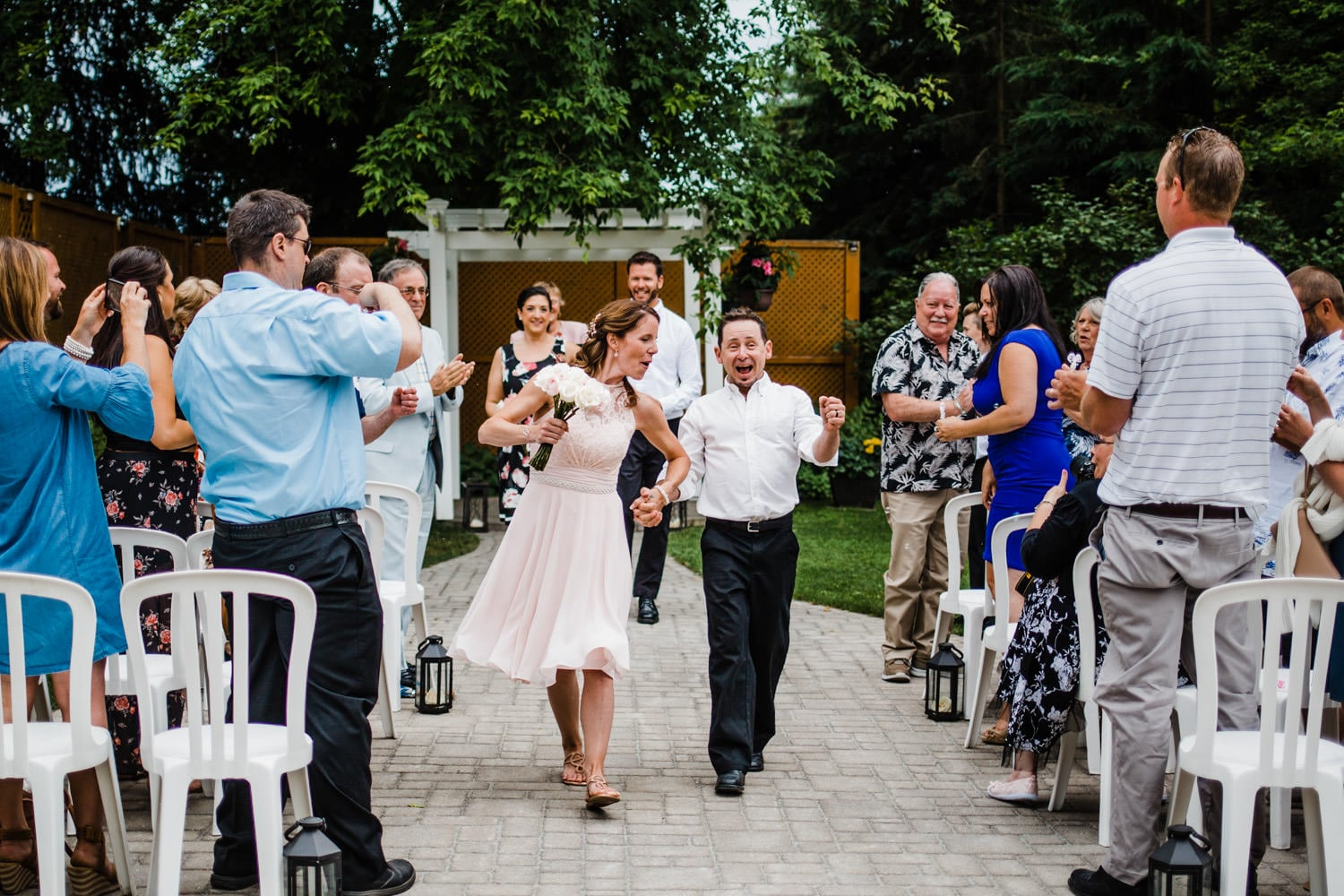 bride and groom excitedly walk out of ceremony - intimate wedding at the schoolhouse