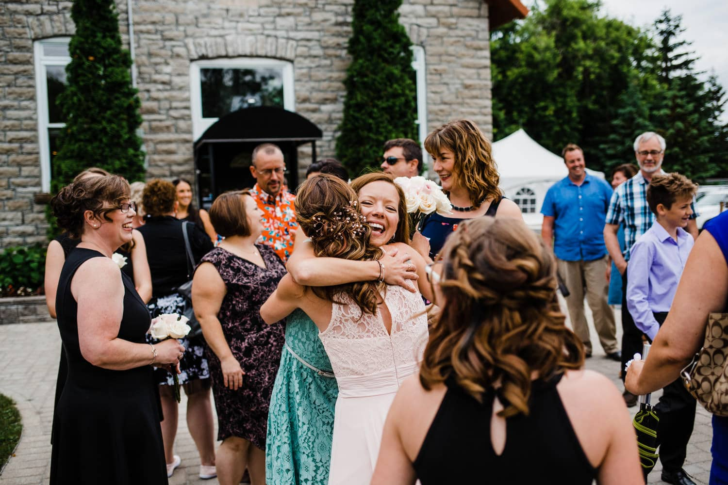 bride celebrates with guests after the ceremony - small outdoor wedding at the schoolhouse