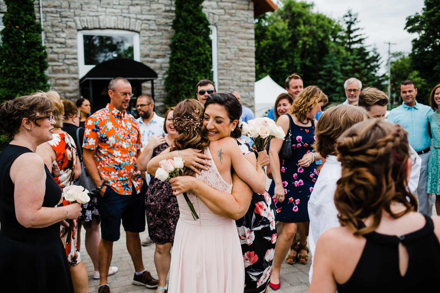 bride celebrates with guests - small outdoor wedding at the schoolhouse