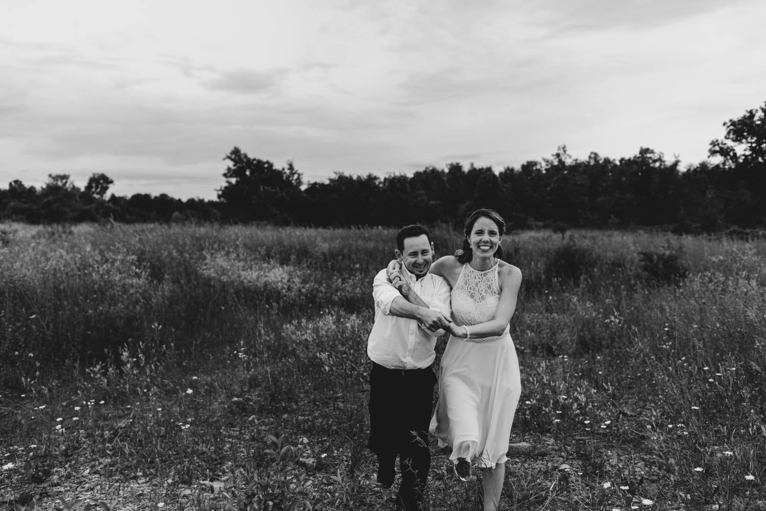 couple dance and laugh together in field - small outdoor wedding ottawa