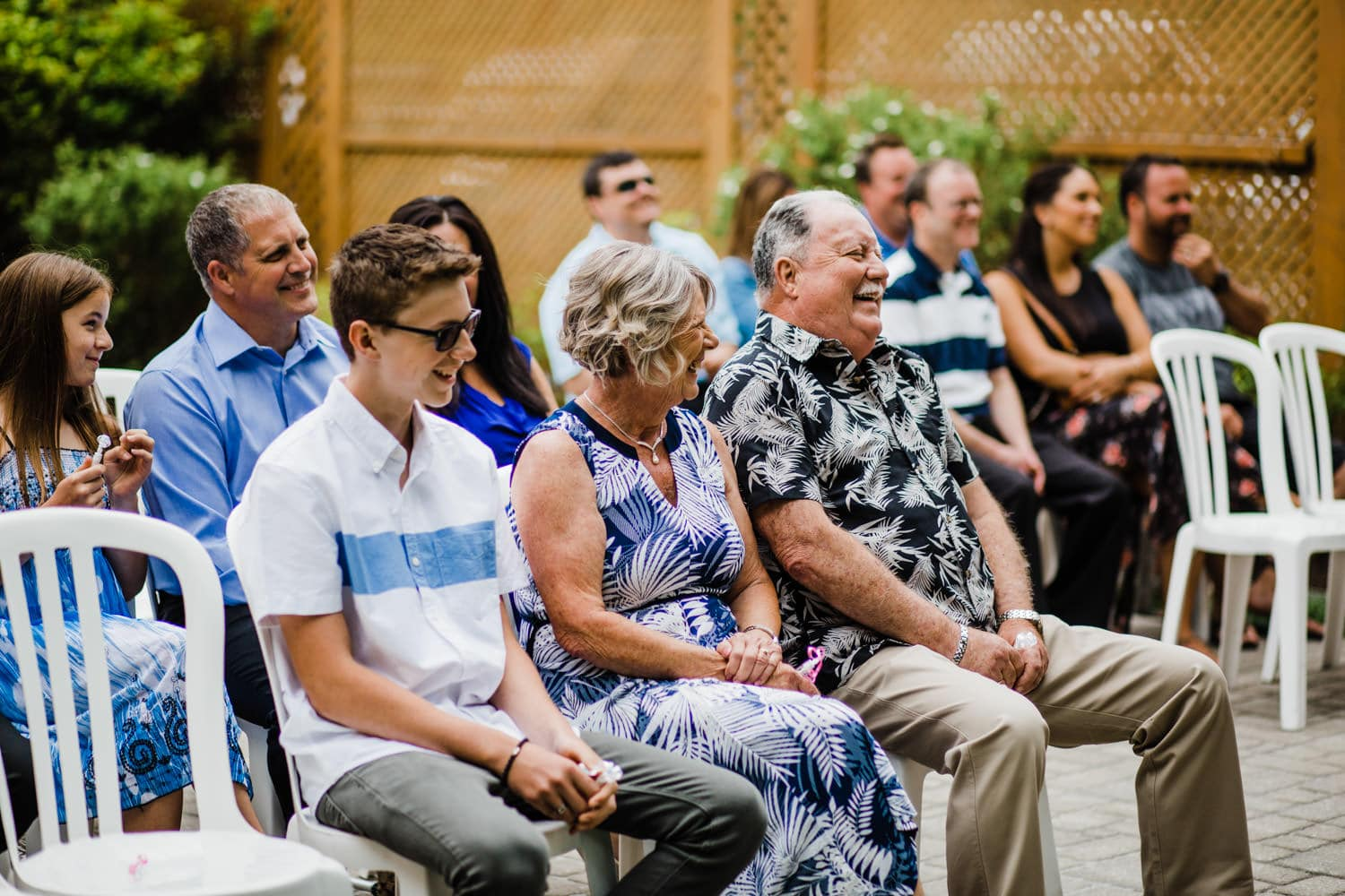 guests laugh during small outdoor wedding ceremony