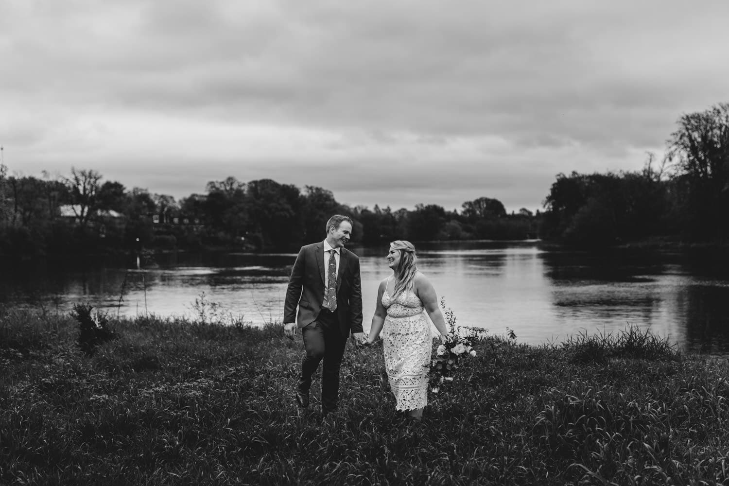 bride and groom walk together near river - small ottawa wedding at The Cameron