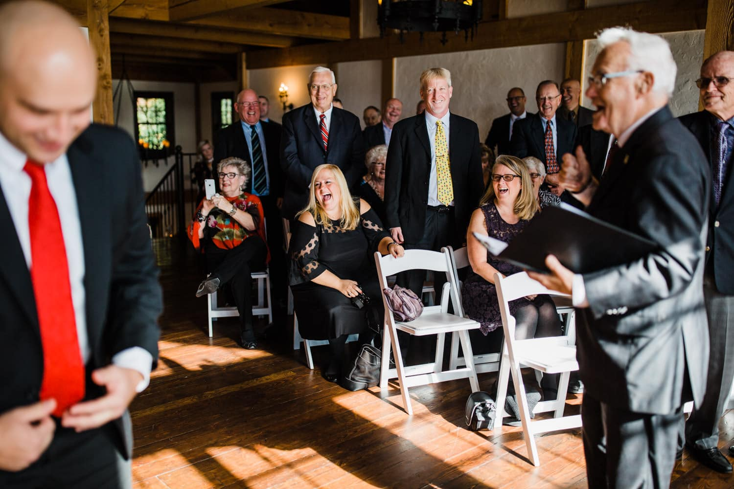 guests laugh during wedding ceremony