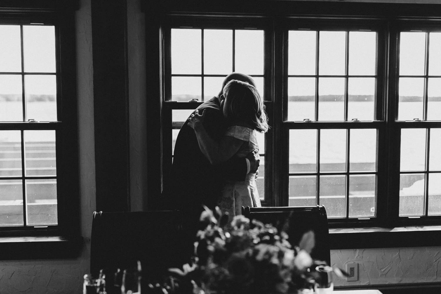 bride and groom hug infront of large windows