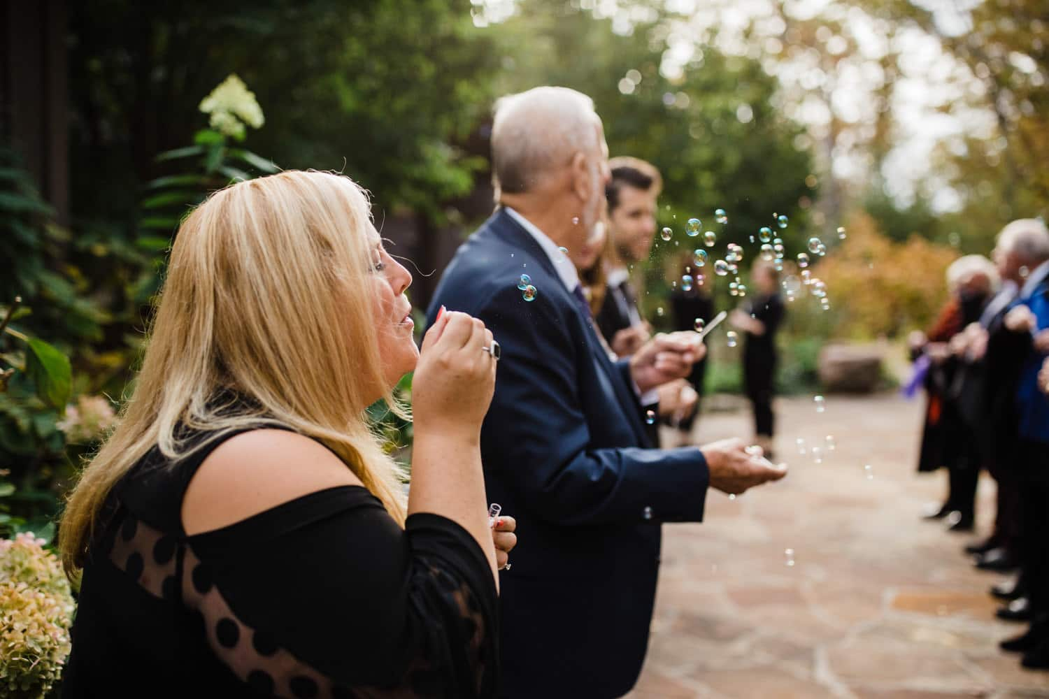 Guests blow bubbles at fall wedding