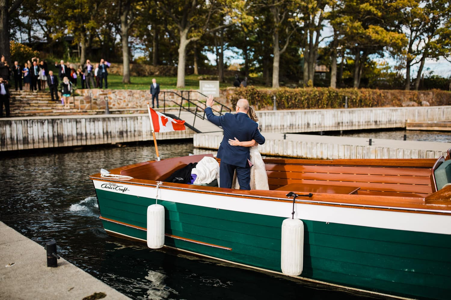 bride and groom make exit on antique boat - thousand islands wedding