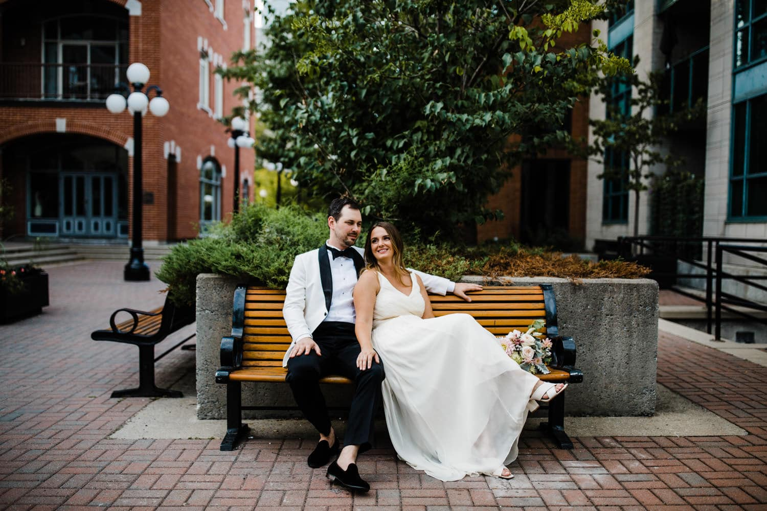 couple sit together in byward market - downtown summer wedding