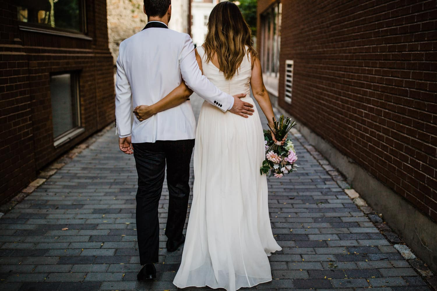 couple walk through alleyway together - summer wedding at the sussex contemporary