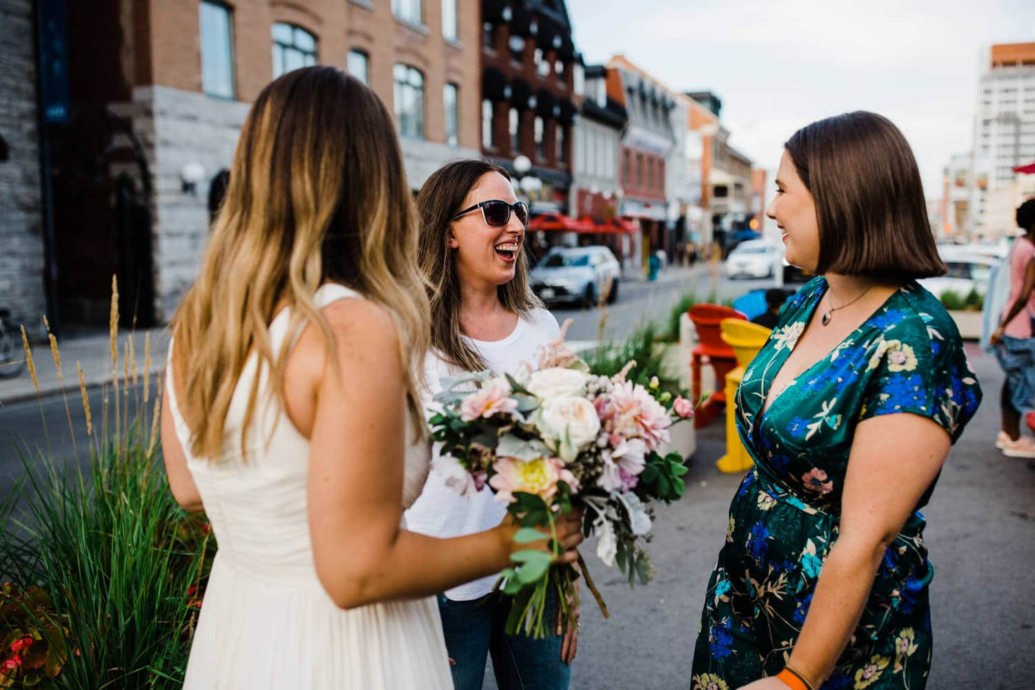 bride laughs with friends in byward market - small ottawa wedding