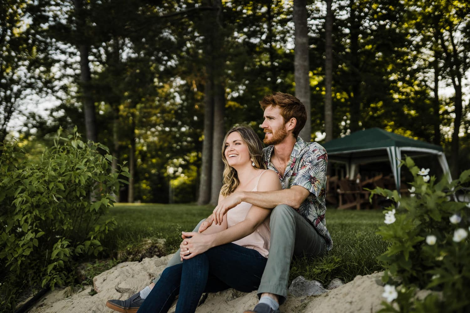 couple look out at lake together - cottage engagement session
