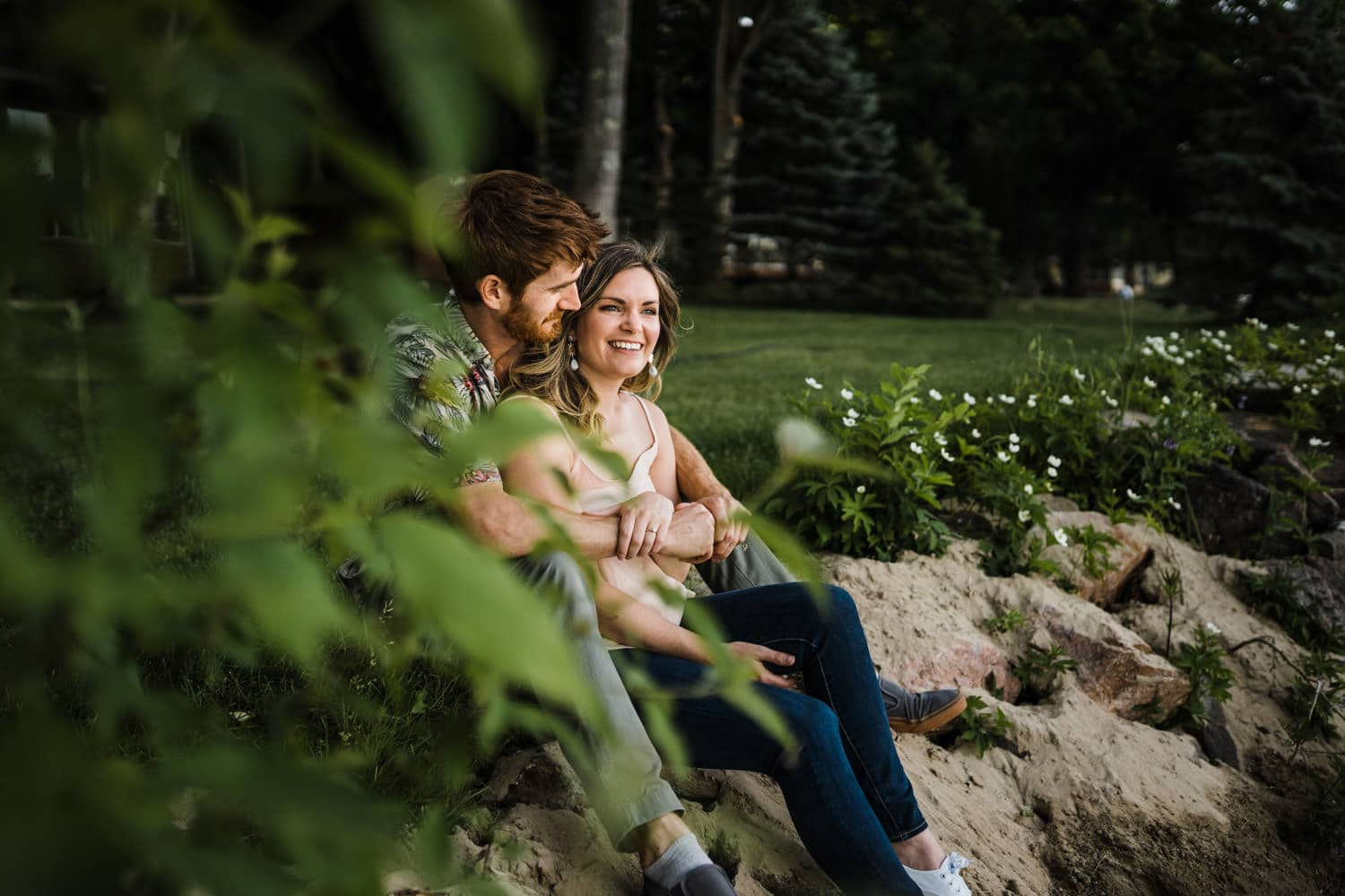 cottage engagement session - couple sit in the sand together