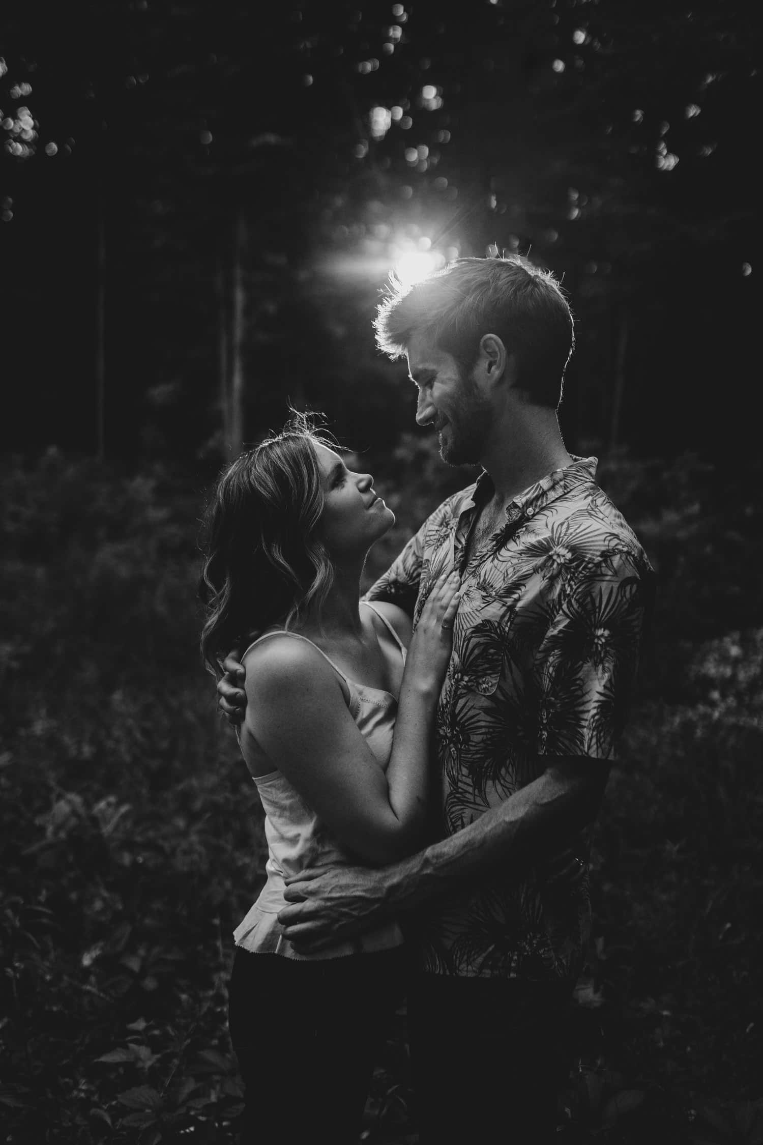 black and white portrait of couple with sun flare behind them