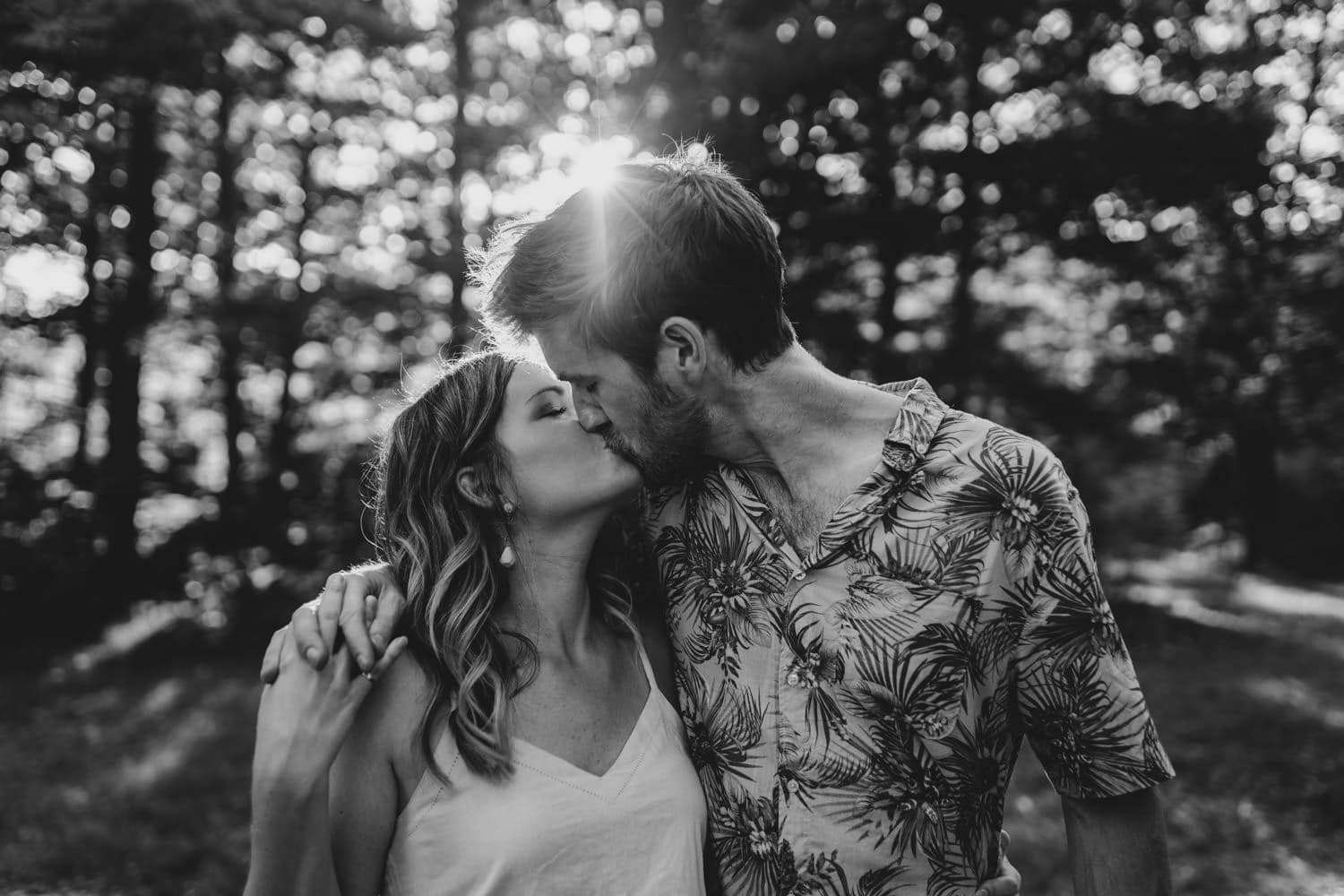 couple kiss in front of wooded area - cottage engagement session