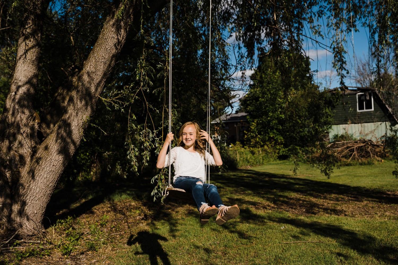 young girl swings on rope swing in backyard