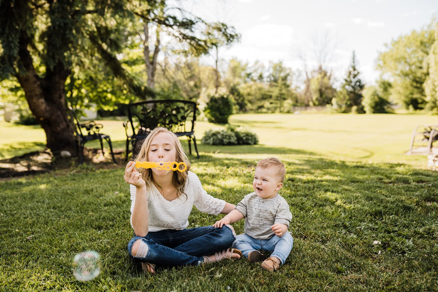 older sister blows bubbles for baby brother - lifestyle family photos ottawa