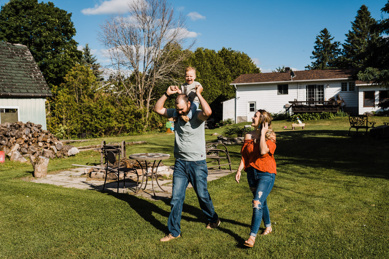 parents walk with their toddler in their backyard