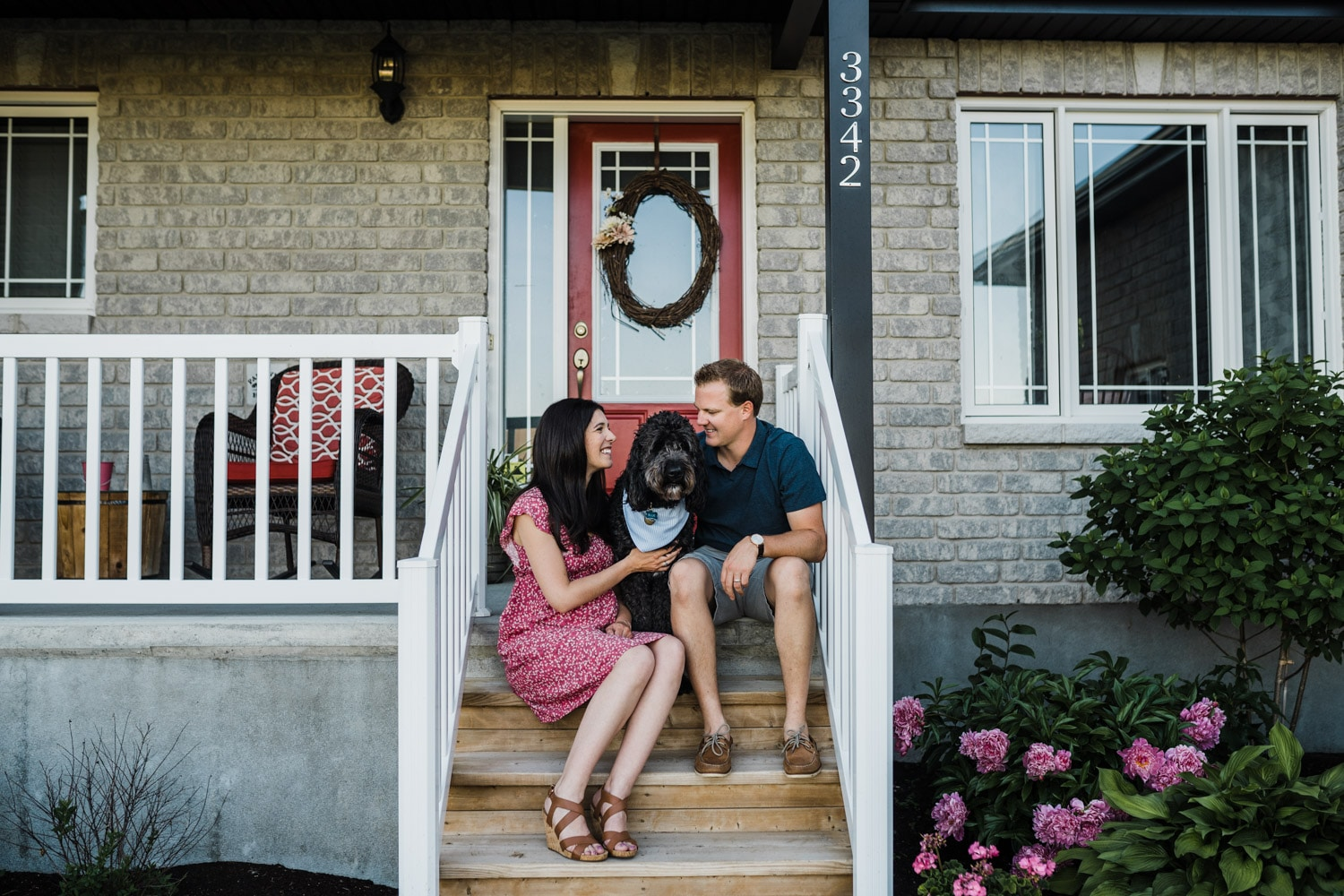 couple sit on front porch with their dog in-between them