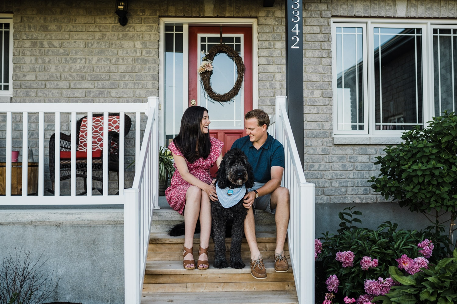 couple sit and laugh on their front porch with their dog - outdoor summer maternity