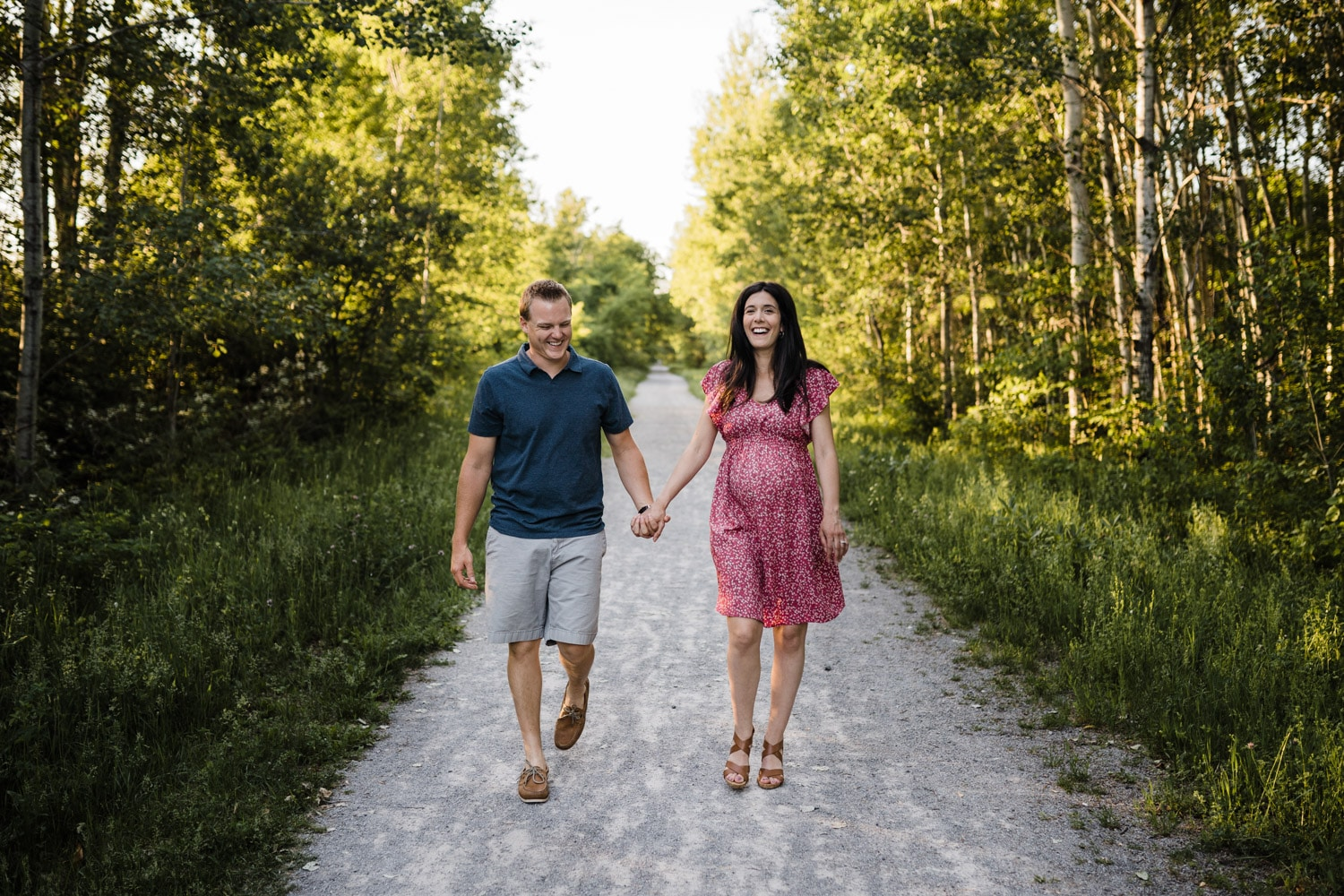 expectant couple laugh and walk together outside