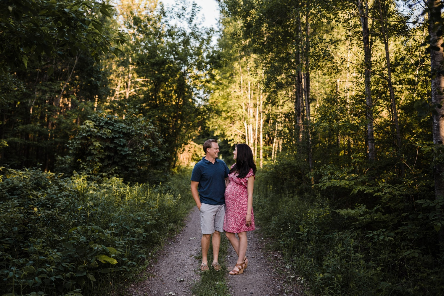 couple stand on pathway together - outdoor summer maternity photos