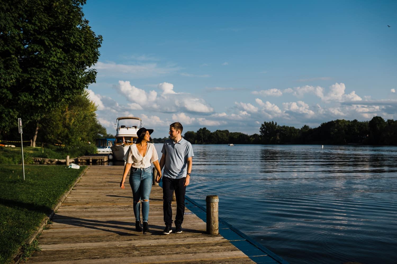 couple walk hand in hand along a dock
