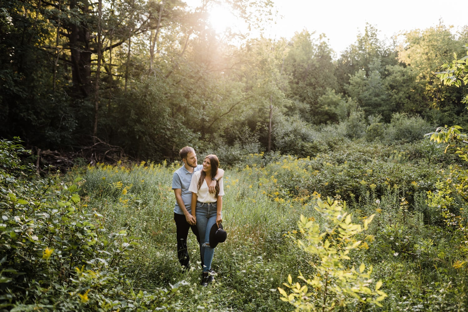 couple stand in tall grass together