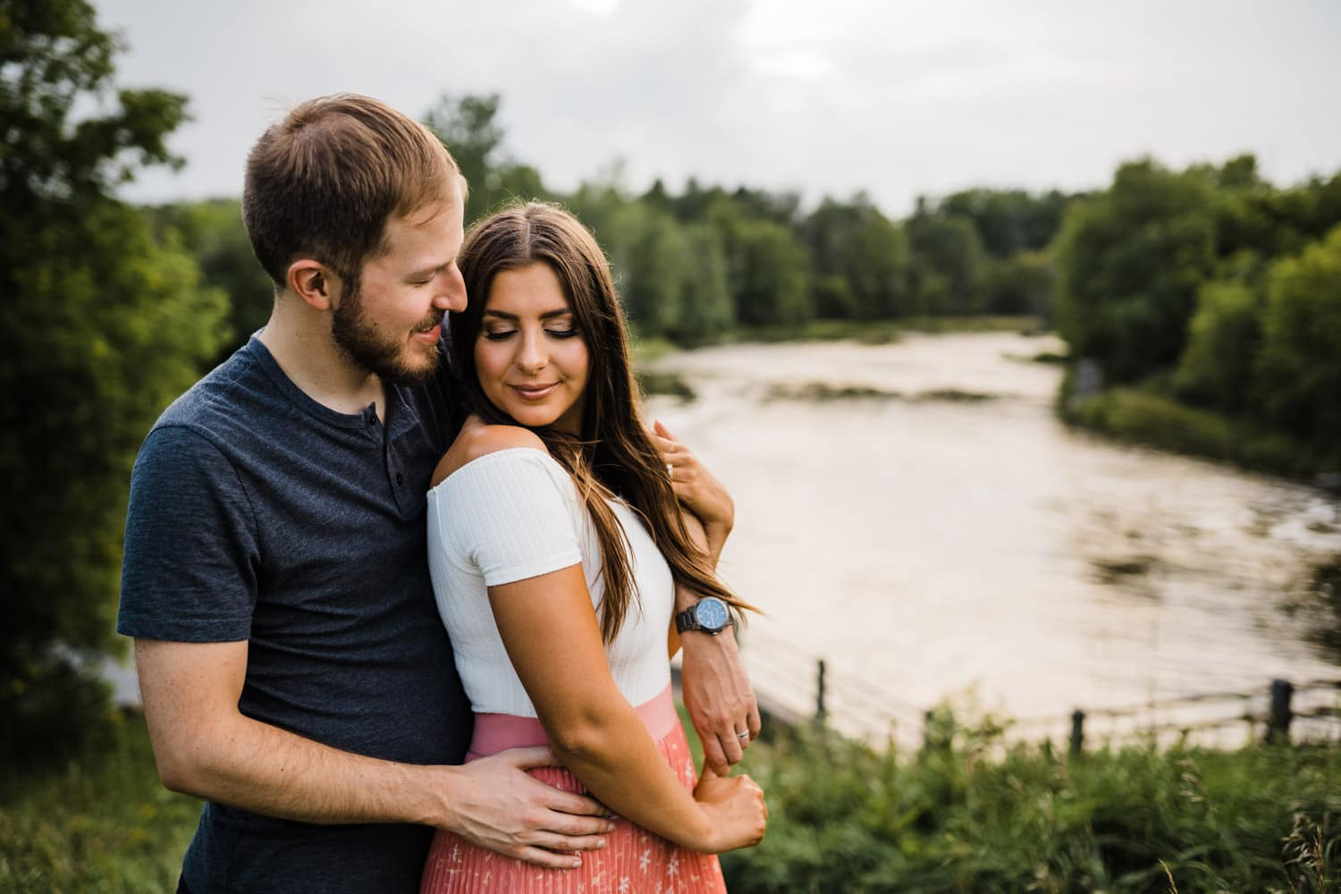 couple snuggle up near river together - ottawa anniversary session