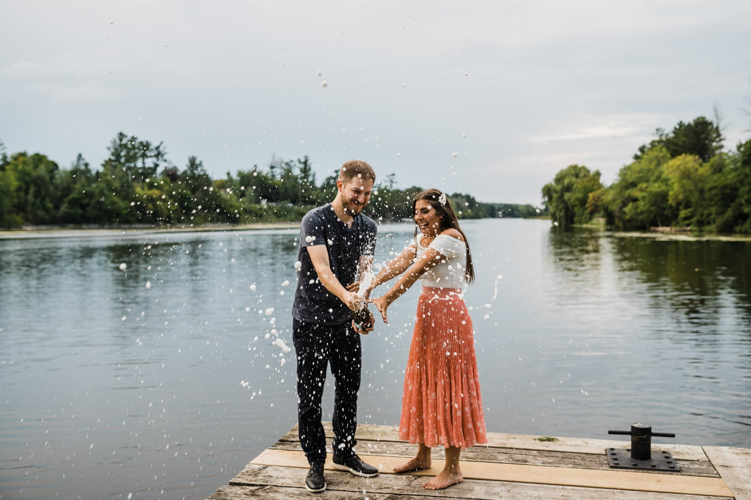 couple pop champagne together on dock - ottawa anniversary session