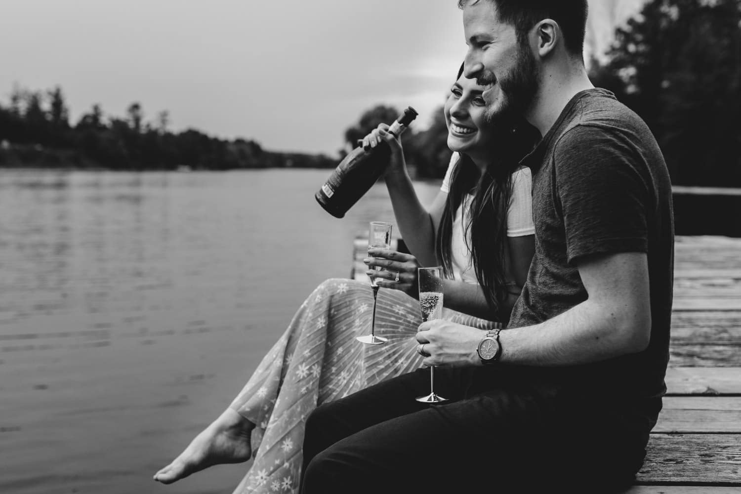 couple sip champagne on dock together - ottawa anniversary session