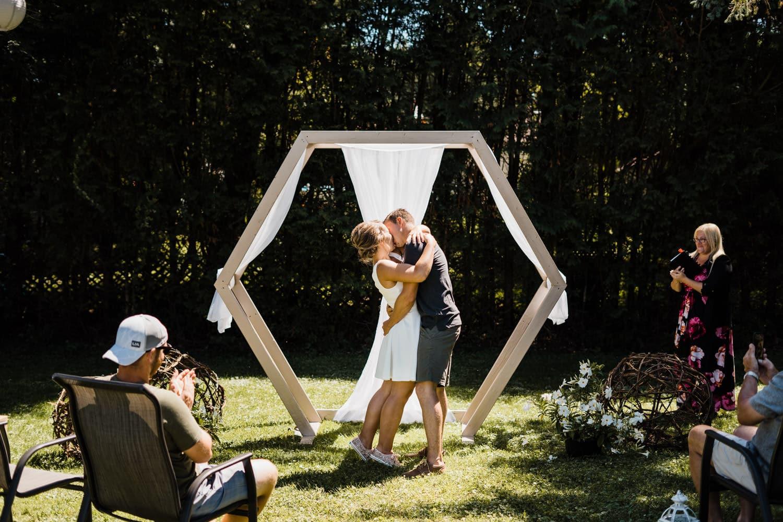 first kiss at backyard wedding bbq