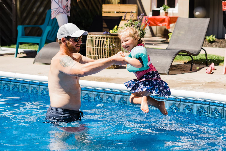 kid jumps into pool at backyard wedding bbq