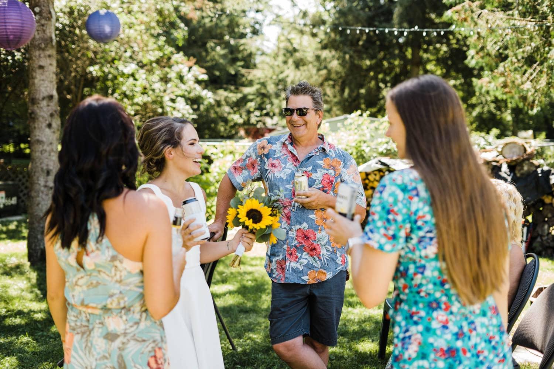 bride and guests laugh at backyard wedding bbq