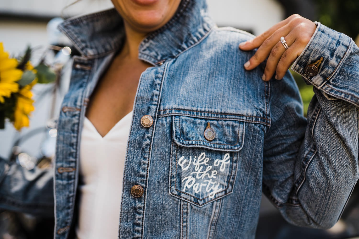 wife of the party detail on wedding jean jacket