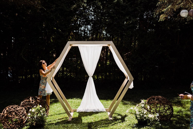bride's friend adjusts the handmade archway for backyard wedding