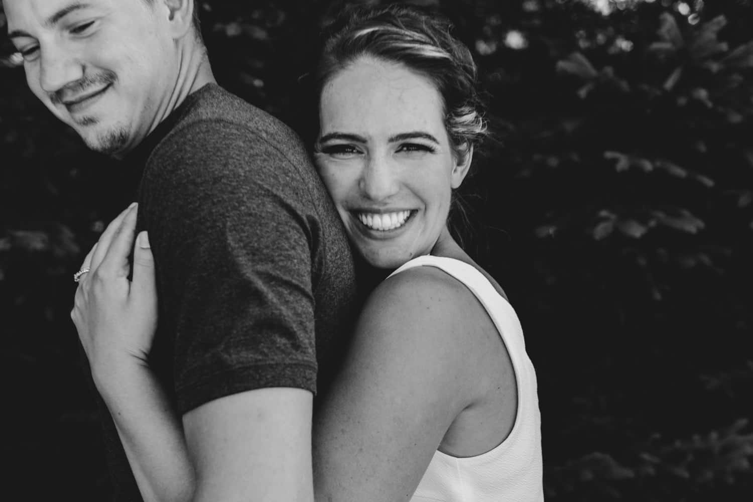 woman hugs husband in black and white portrait