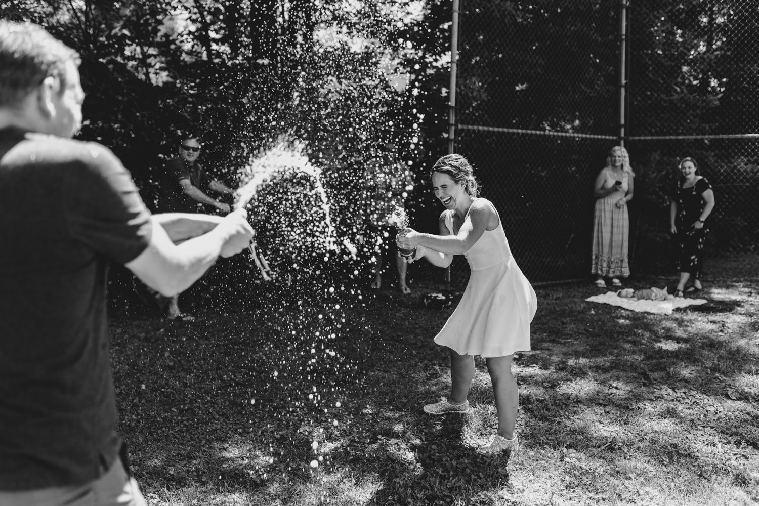 bride and groom spray champagne at one another