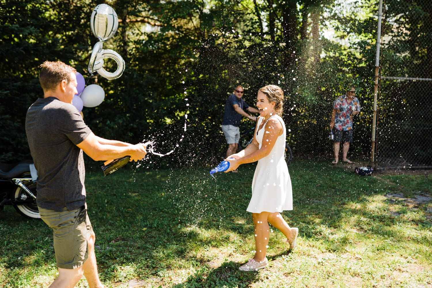 bride and groom shake champagne at one another - backyard wedding bbq