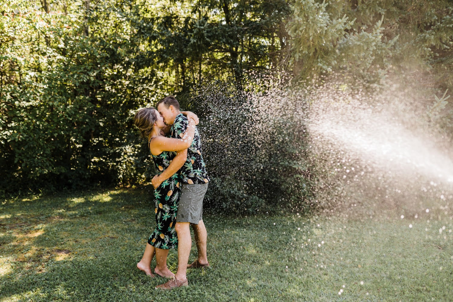 bride and groom kiss as champagne is sprayed at them