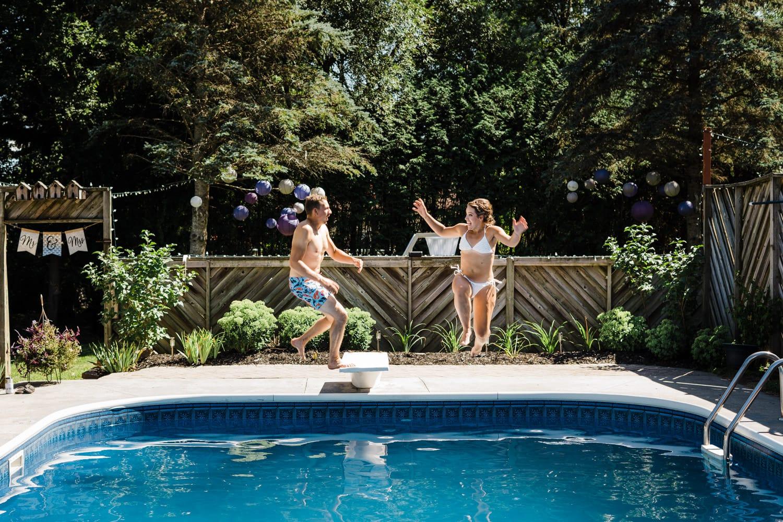 bride and groom jump into pool after small backyard wedding