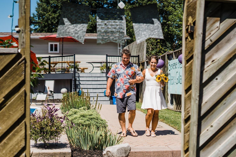bride walks with her dad toward small backyard wedding