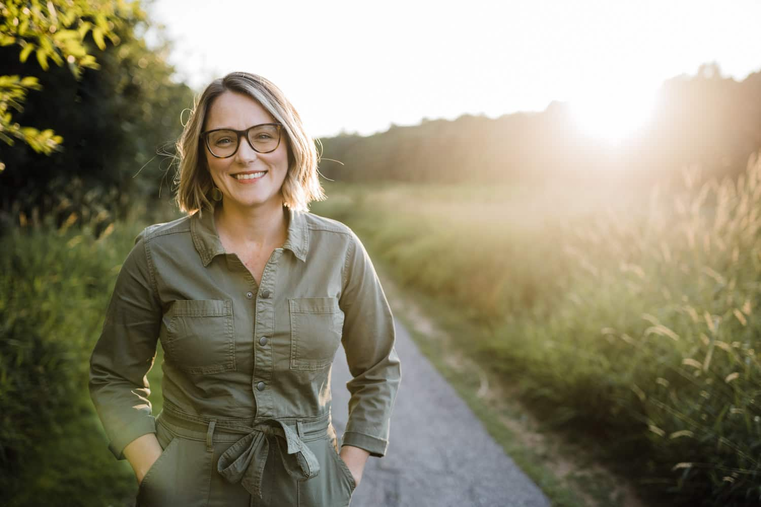 woman stand along a sun soaked path during golden hour - ottawa brand photography