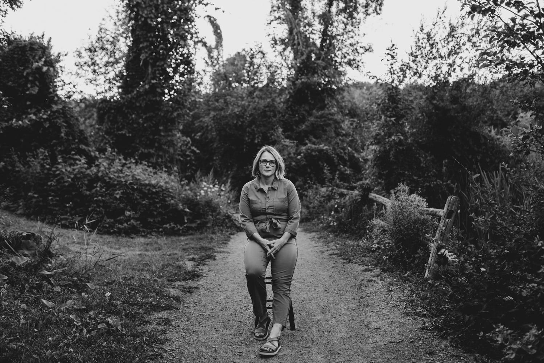 woman sits on stool along a forested pathway - ottawa brand photography - ottawa lifestyle portraits