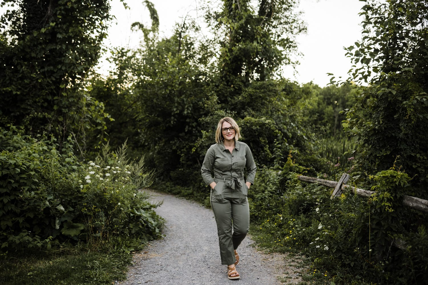 woman walks along forested pathway