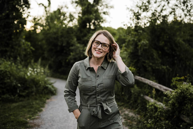 woman walks along pathway and tucks hair behind her ear