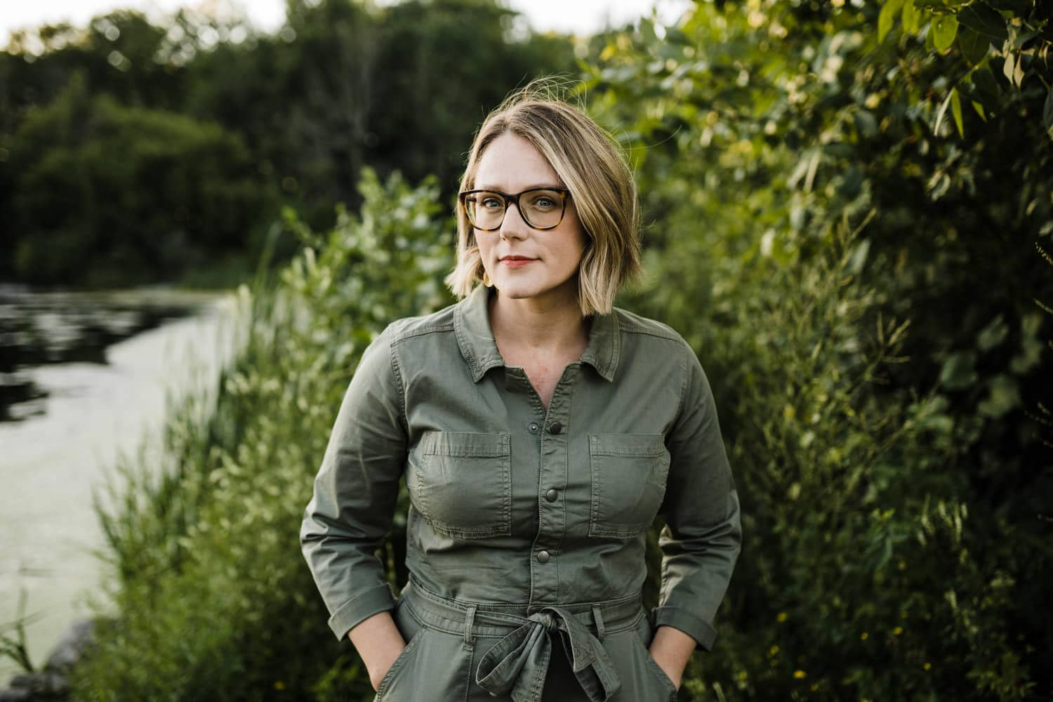 portrait of woman looking at the camera, standing next to a forest - ottawa brand photography